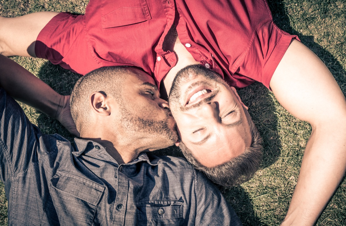 Multicultural gay couple laying in grass kiss on check