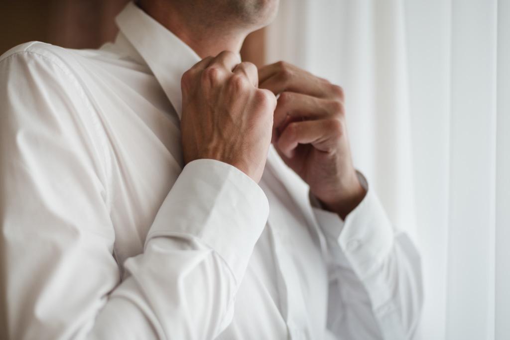 man buttoning white collar shirt