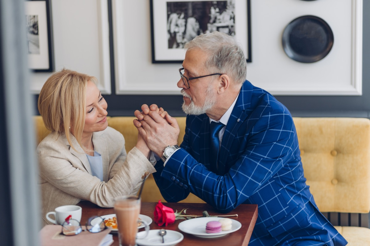 Older man complimenting woman on romantic date