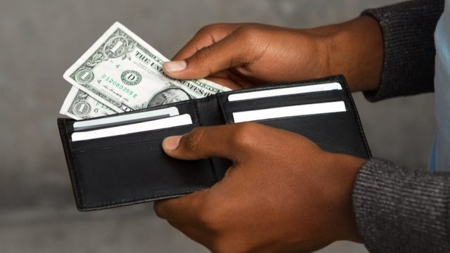 man taking money out of a wallet, parenting is harder