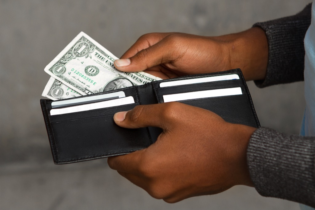 man taking money out of a wallet
