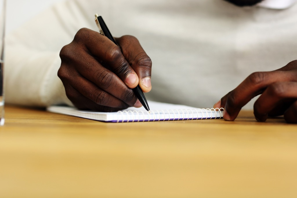 man writing in notebook, ways to feel amazing