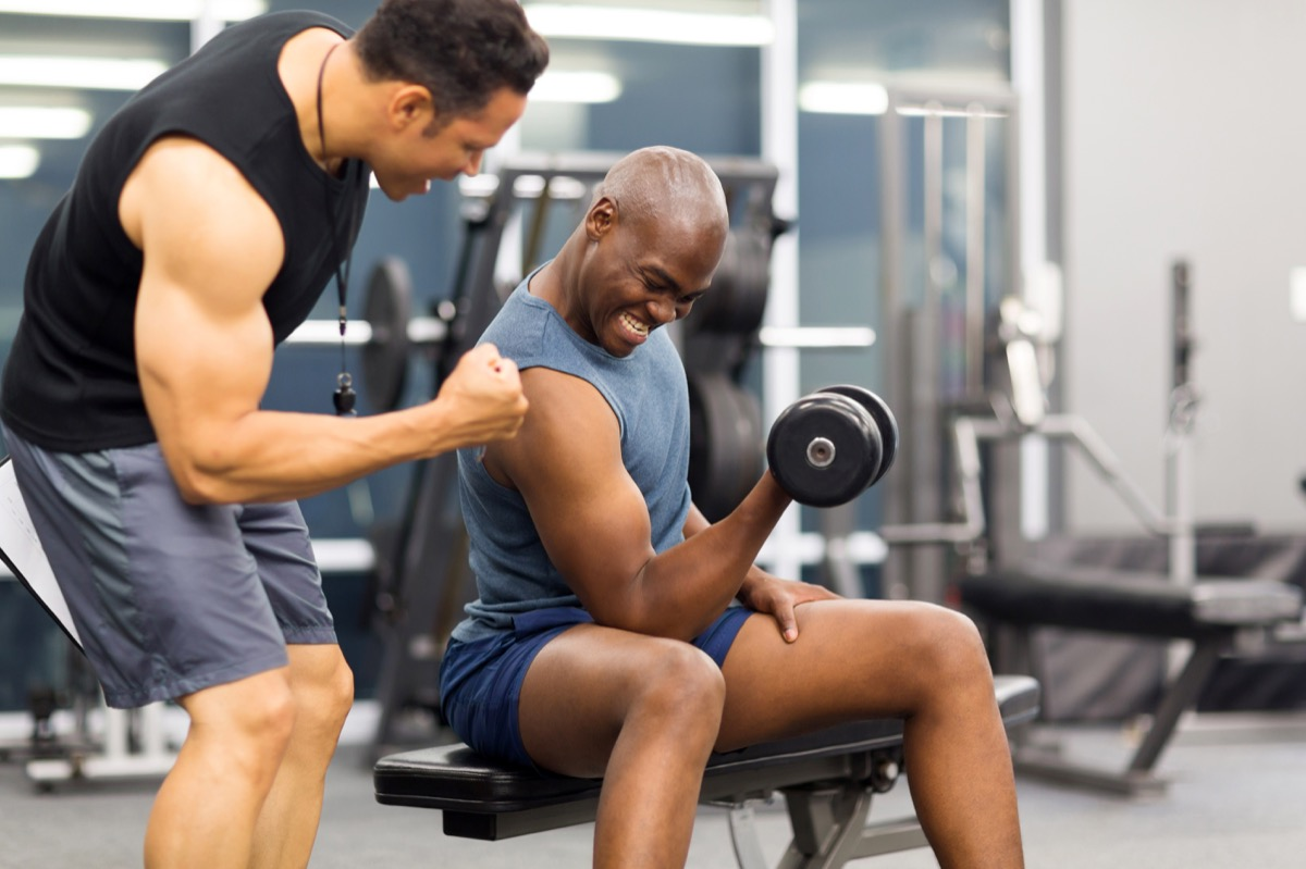 Multicultural men lifting weights in gym helping
