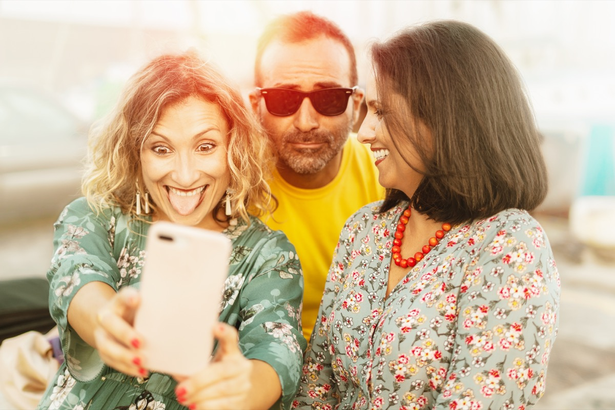 Middle aged friends being silly having fun taking selfies with phone