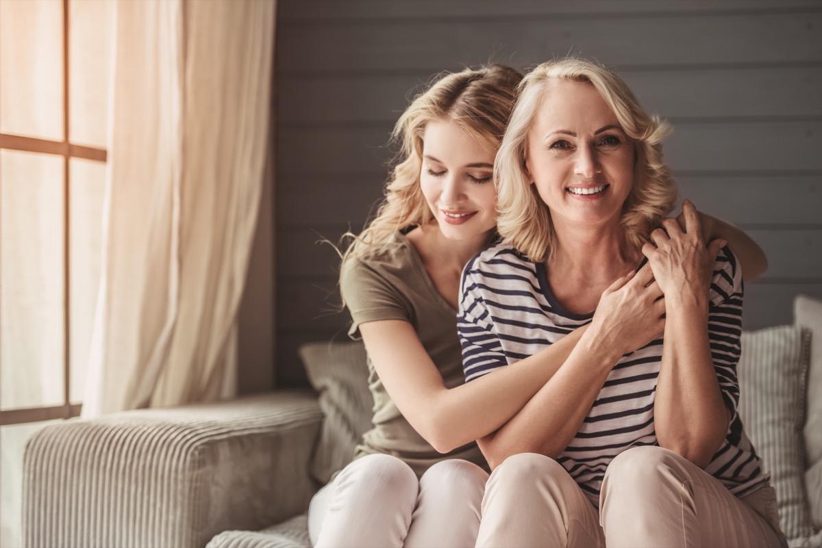 Adult daughter hugging mother smiling