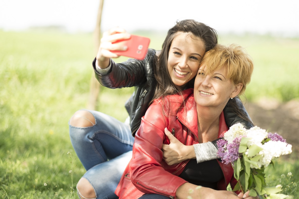 Mother and daughter taking a selfie with flowers