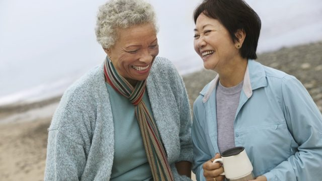 Multicultural middle aged women laughing on the beach