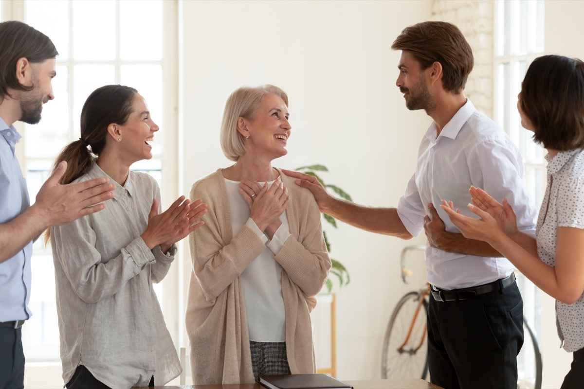 Older woman receiving compliments thankful to coworkers