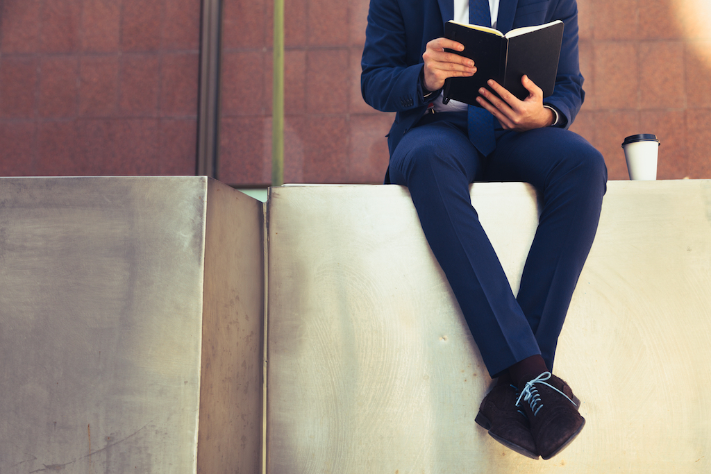 man on a ledge reading a book in a suit - how to dress over 50