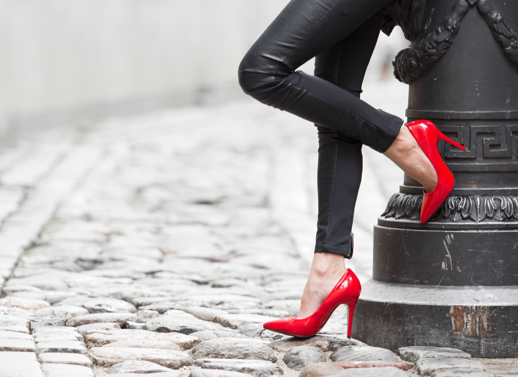 woman in red shoes leaning against a lamppost - how to dress over 50