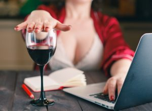 woman turns down glass of wine