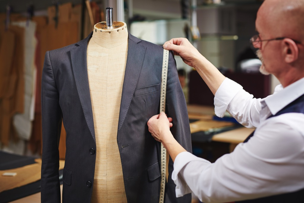 tailor fitting a suit with a measuring tape