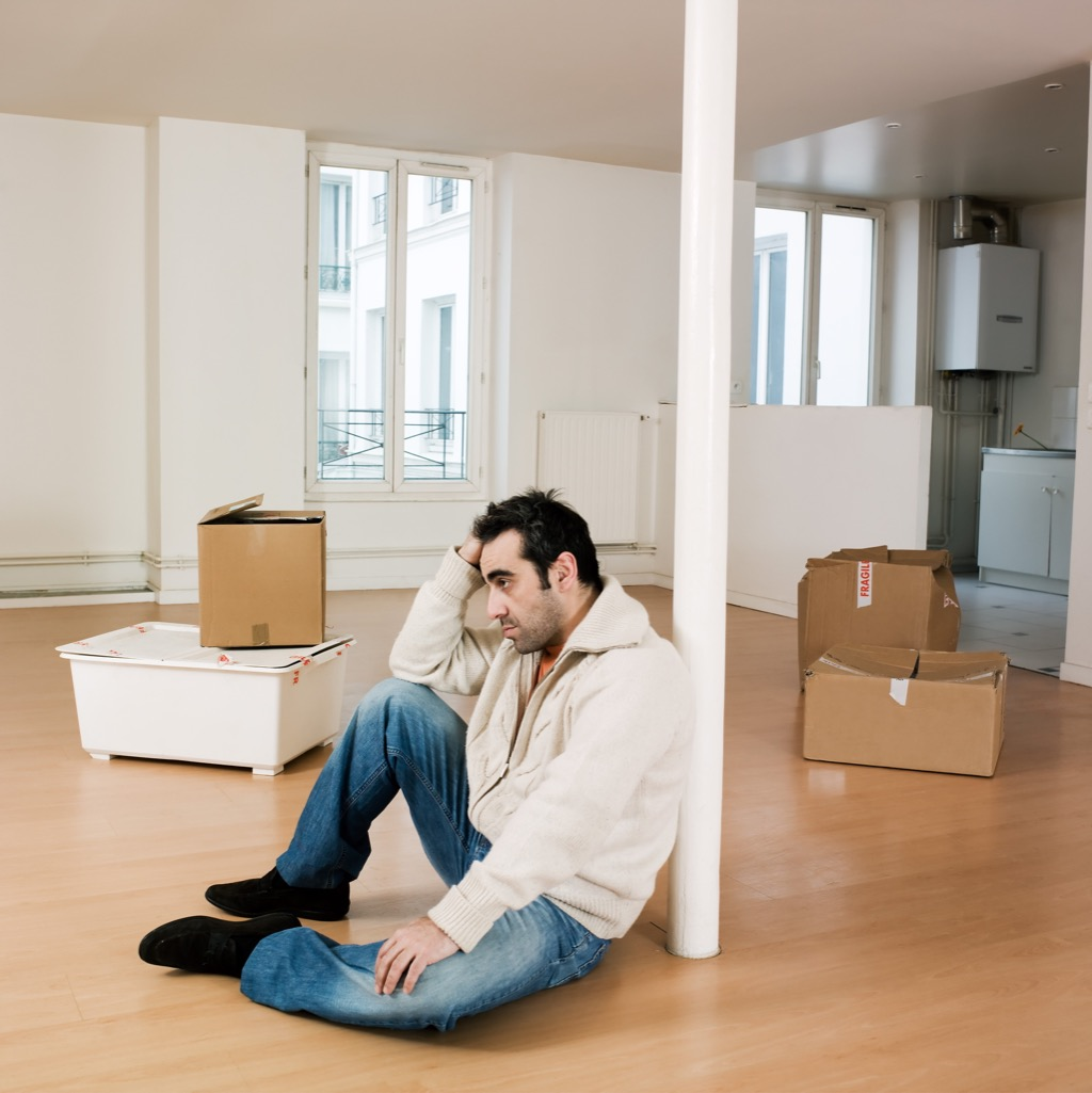 man alone in empty apartment because of divorce preparation
