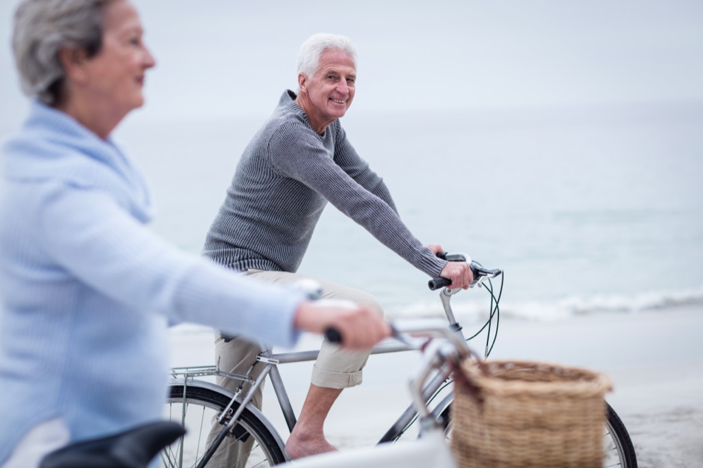 man and woman riding bikes on beach - how to dress over 50
