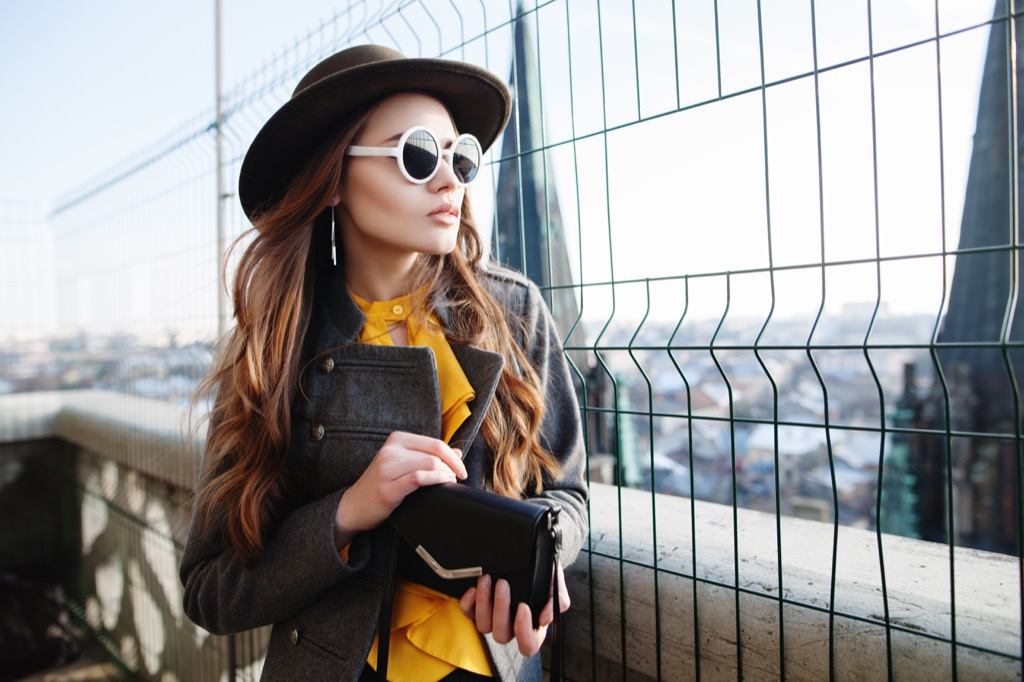 woman model hat outdoors small purse clutch