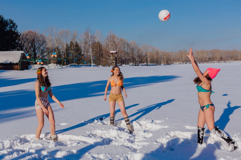 women in bikinis playing volleyball in snow