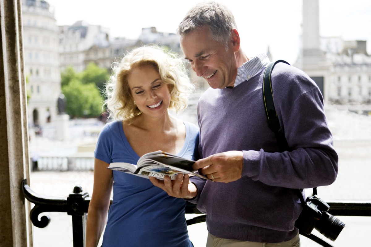 Tourist couple reading book on London sights before sightseeing