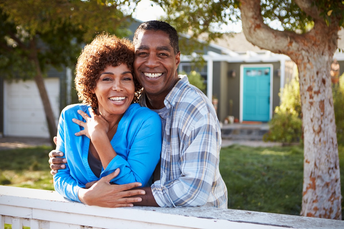 Black couple smiling in embrace on front lawn in sunshine