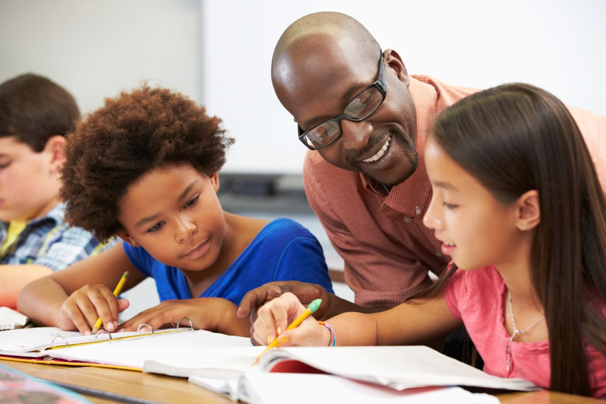 Male teacher helping multicultural students