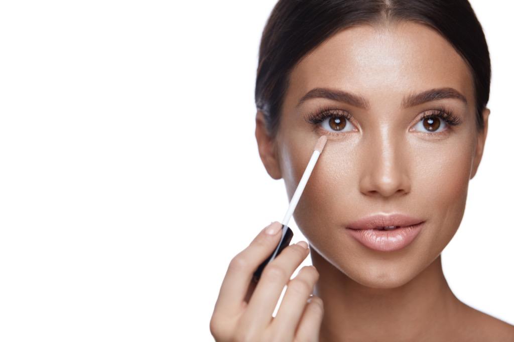 woman applying concealer makeup Body Flaws
