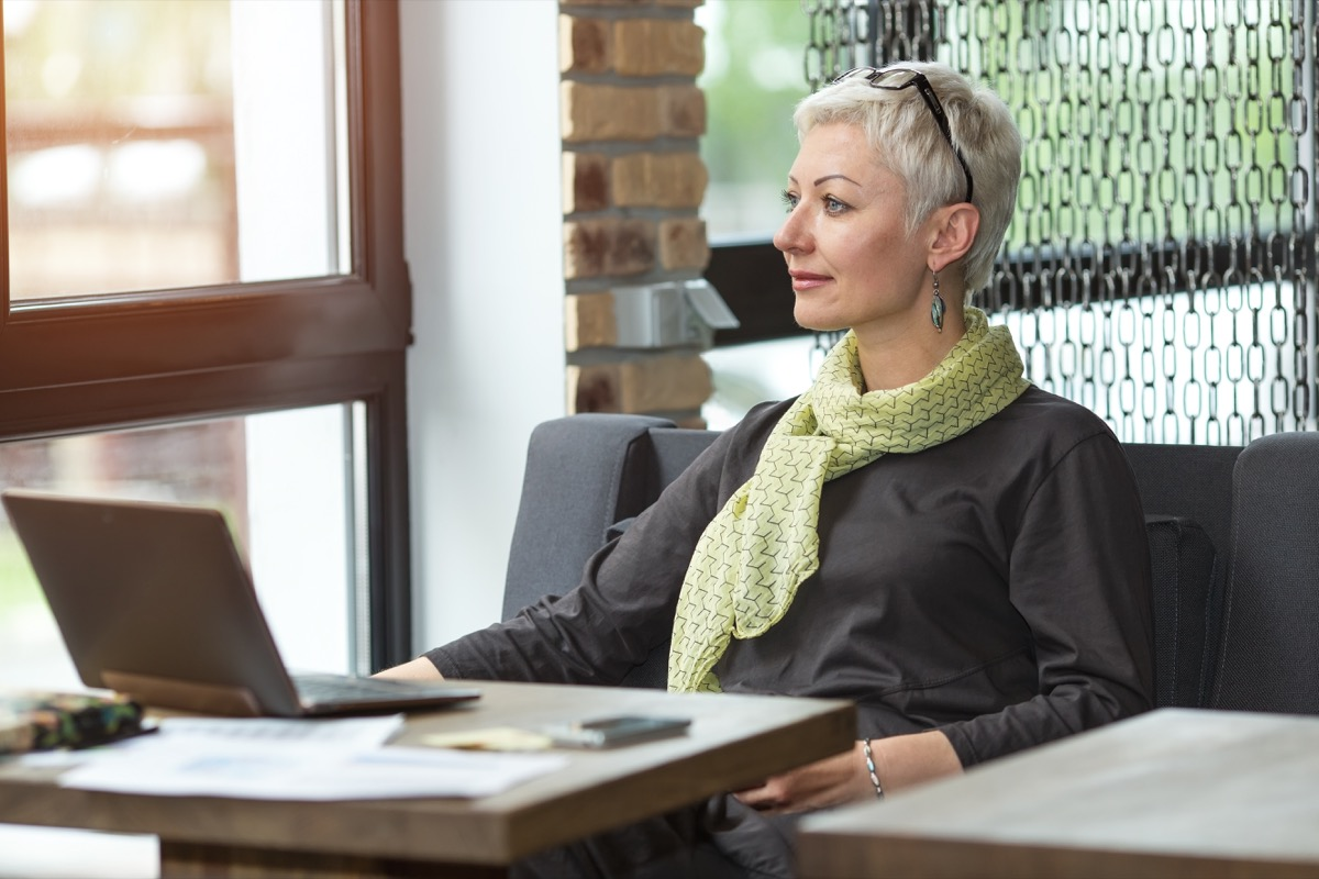 Woman doing work on laptop sitting in deep thought looking out the window