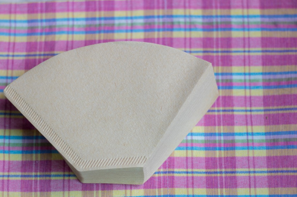 stack of brown coffee filters on pink and blue plaid tablecloth