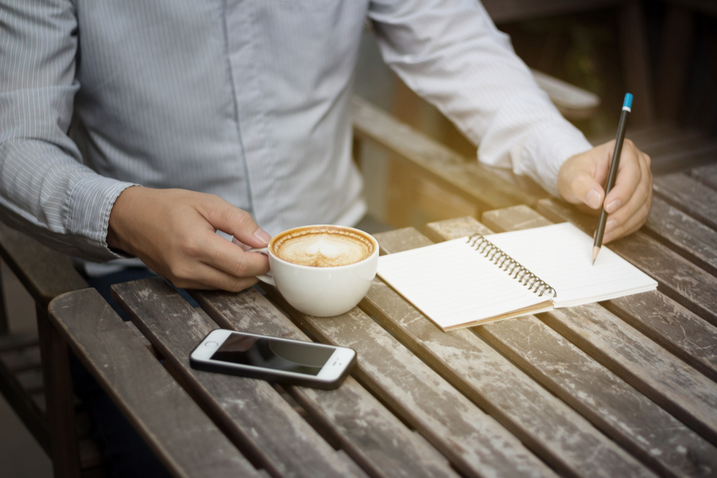 Man Drinking Coffee and Writing Surprising Weight-Loss Tips