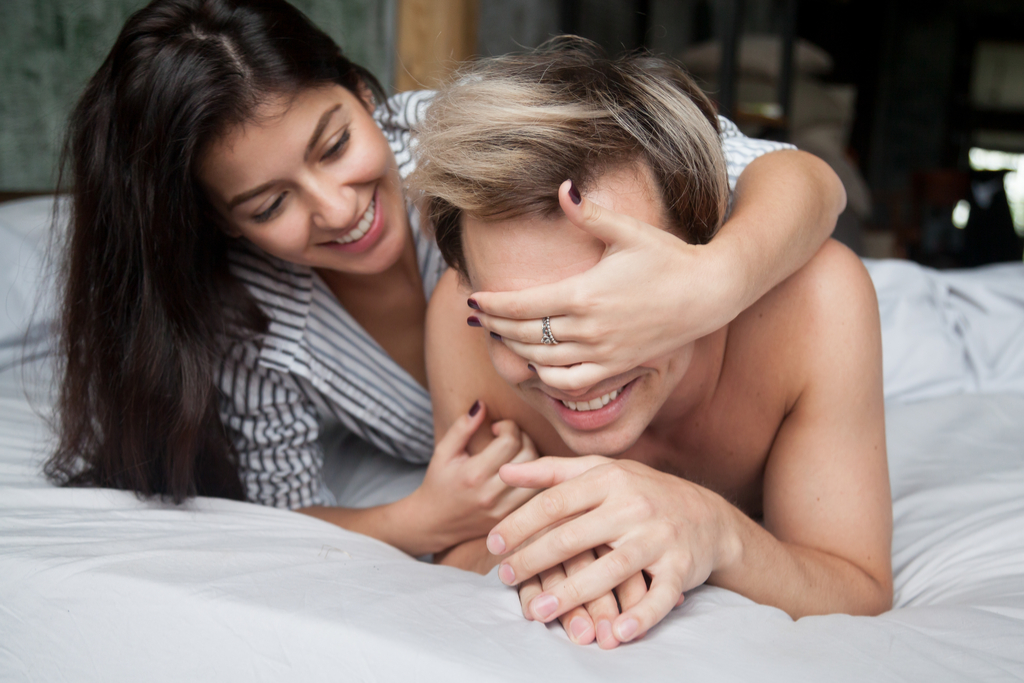 Woman Covering Man's Eyes in Bed Romance
