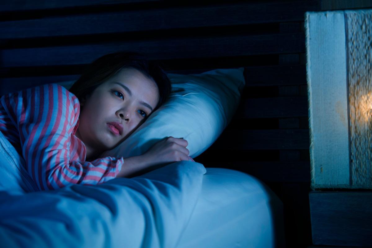asian woman awake in bed