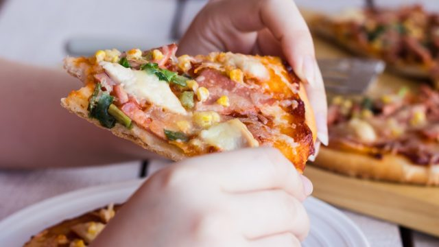 man eating a slide of folded pizza, best way to reheat pizza in oven