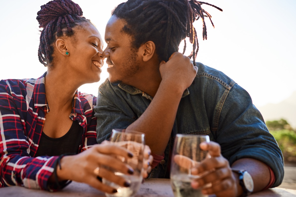 Black couple kissing and enjoying some wine on a date