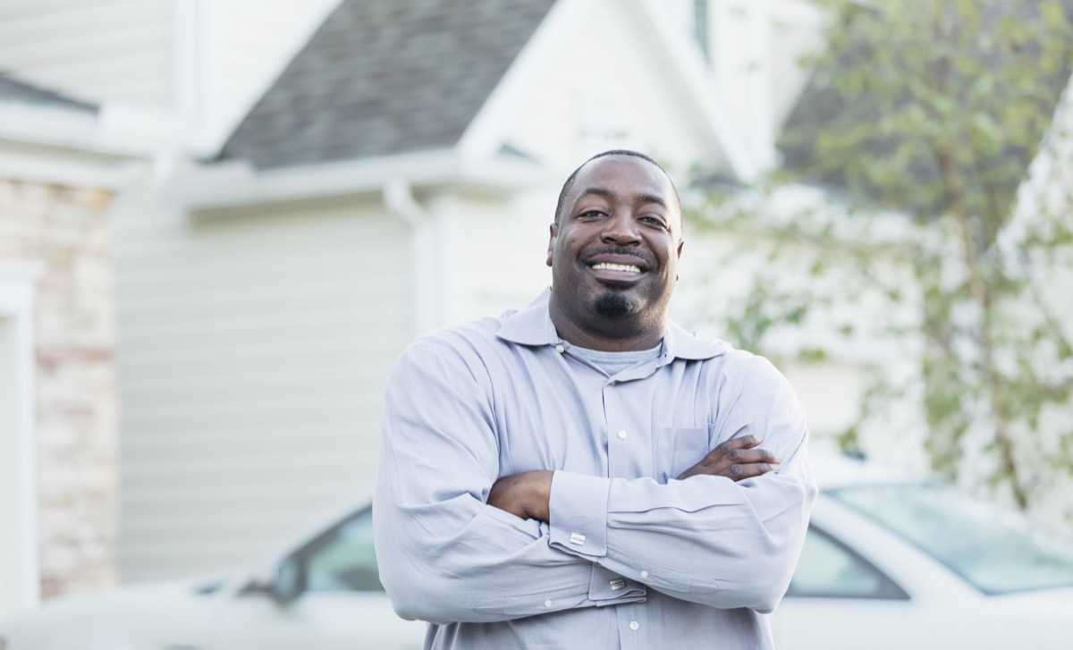 A mature African-American man in his 40s standing outdoors by the driveway of his home, smiling at the camera with his arms crossed.