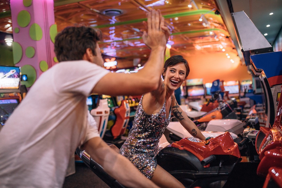 Couple giving high five to each other while playing bike racing games at a gaming arcade. Couple enjoying arcade racing games at a gaming parlour