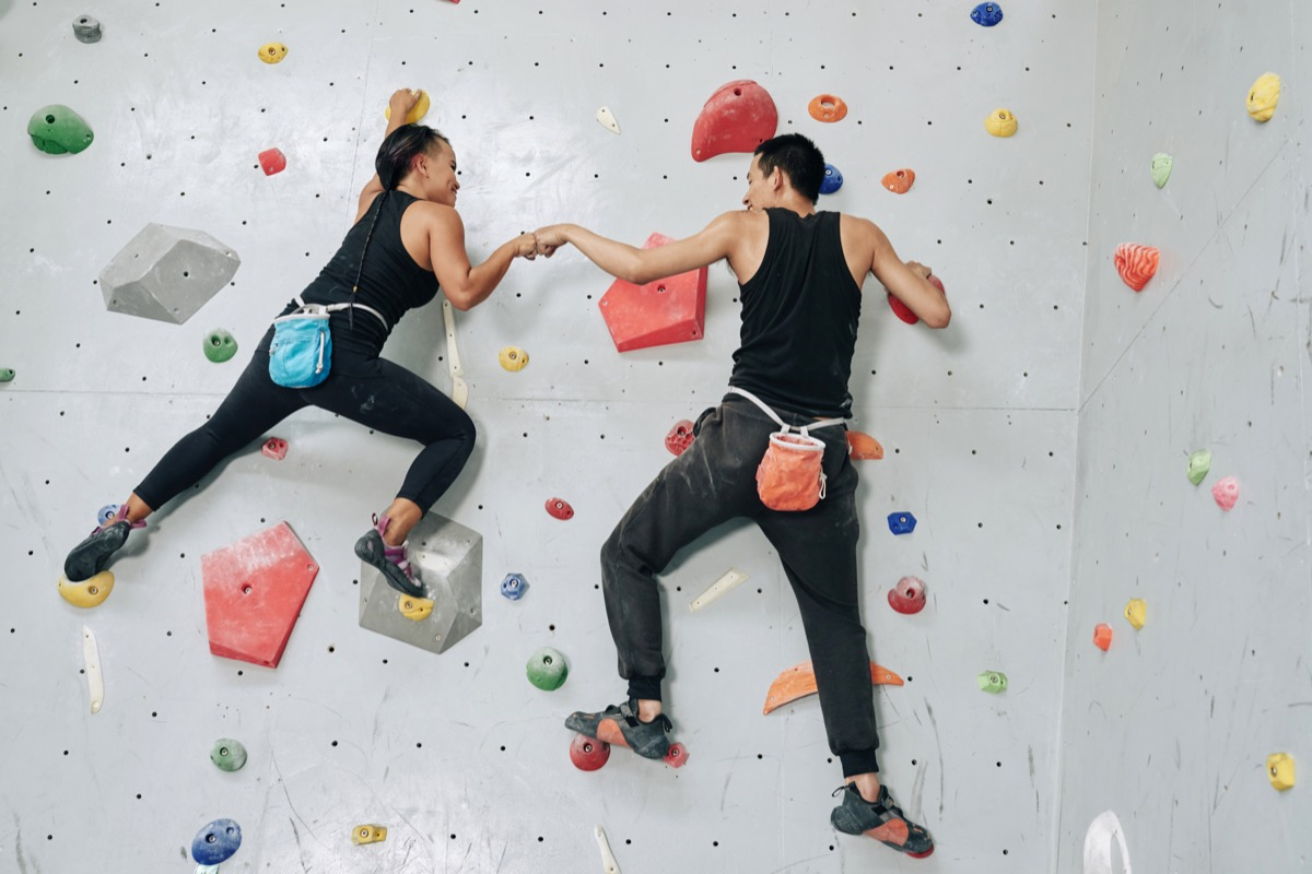 Back view man and woman working out in team and hitting hands while hanging on rock climbing wall
