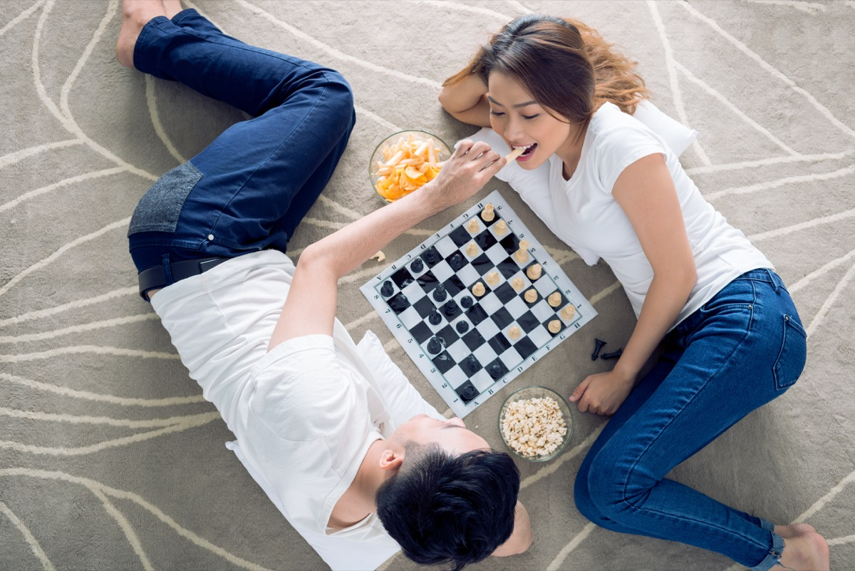 Couple having a board game date night playing chess