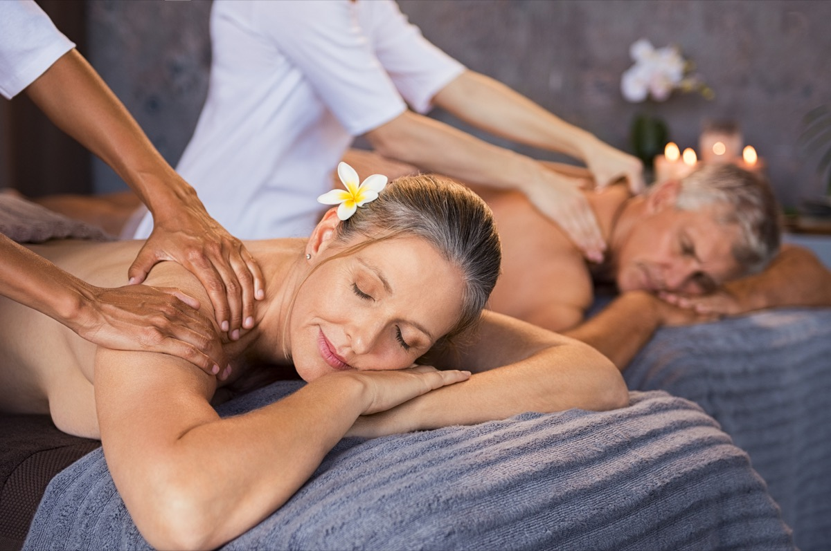 Senior couple in spa salon getting massage. Relaxed senior couple enjoying body treatment in a wellness center. Retired man and woman receiving a back massage from masseur in a spa salon. (Senior couple in spa salon getting massage.