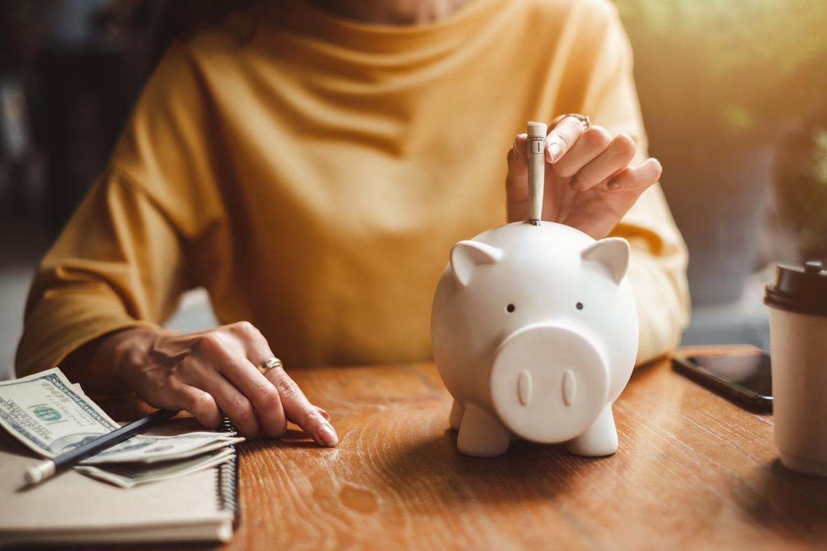 close up of woman putting dollar bills in a piggy bank