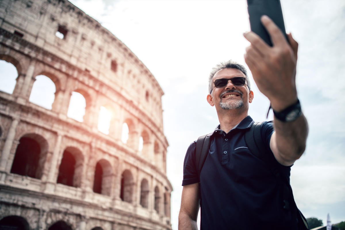 middle aged white man taking a selfie in front of the colosseum