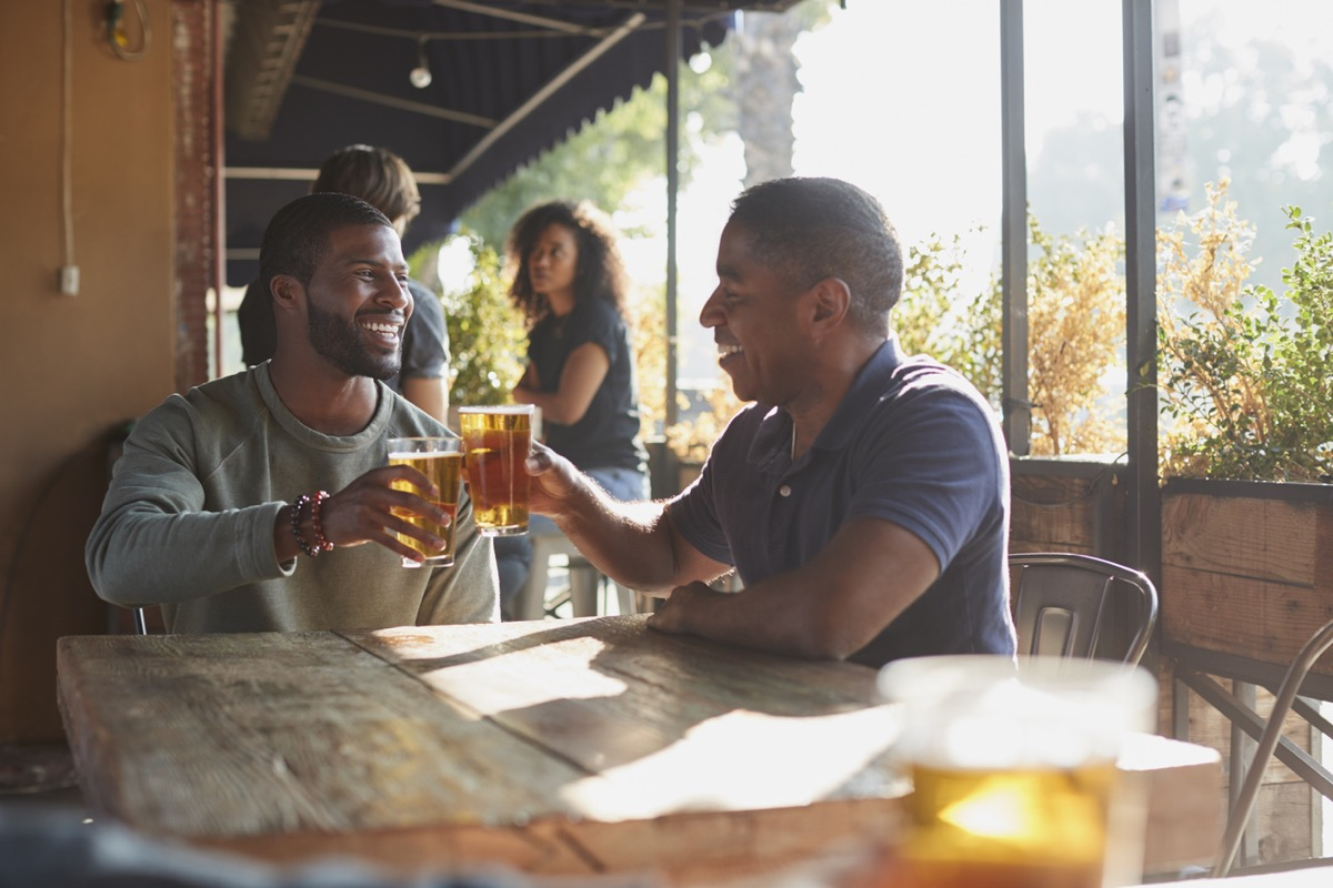 two middle aged black man toasting beer on the patio at a sports bar