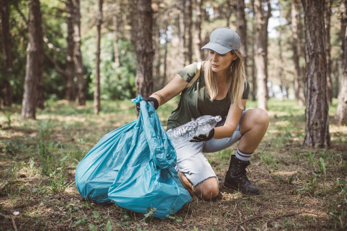 white woman putting a plastic bottle in a large bag in a park