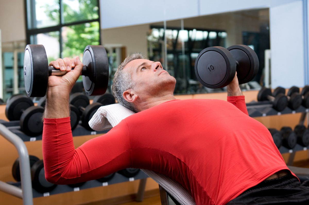 middle aged white man lifting weights at the gym