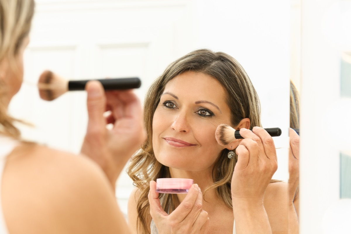 middle aged white woman applying blush