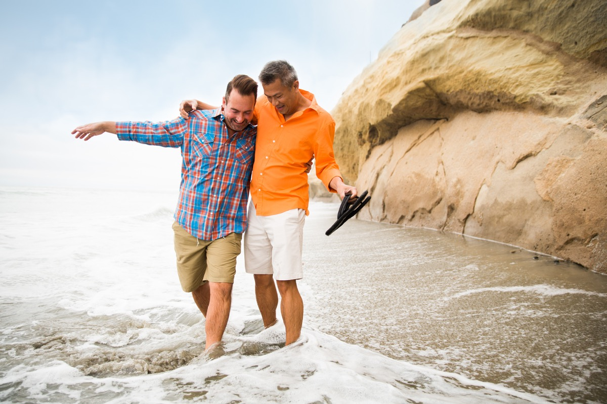 white man and asian man embracing and avoiding the waves on a beach