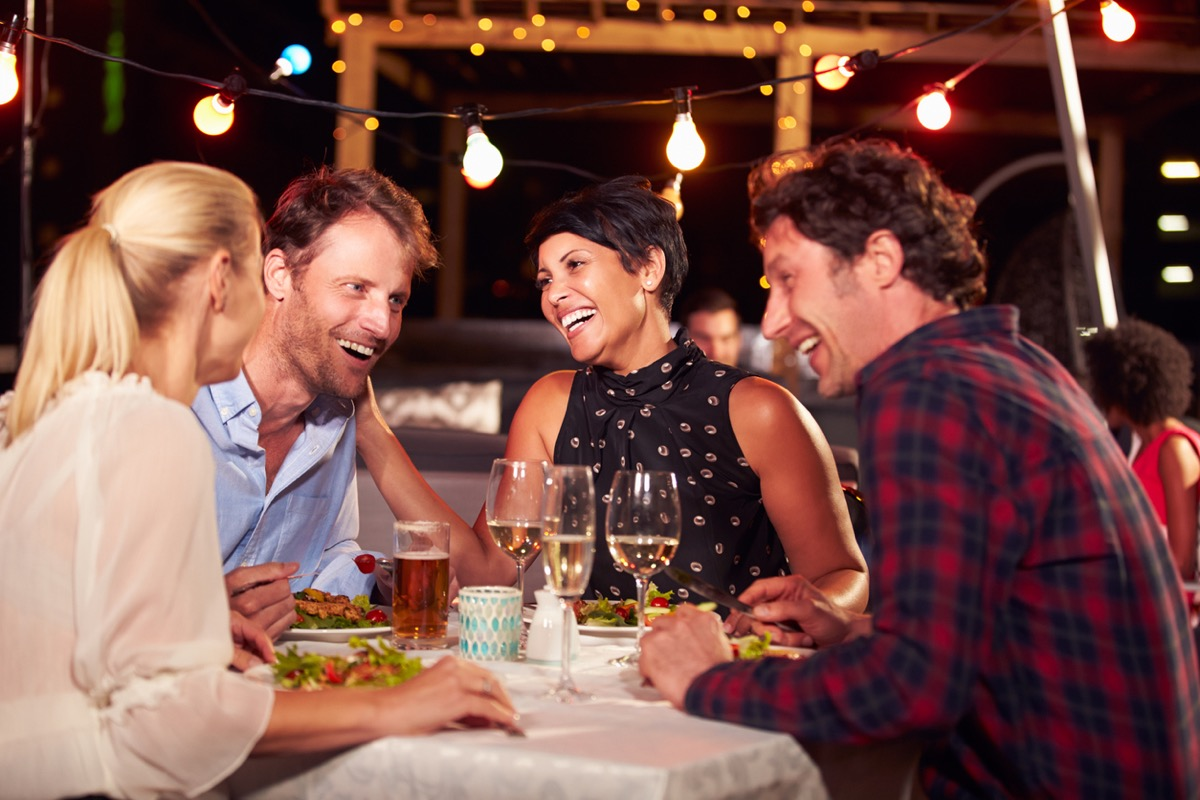 group of four friends having dinner on a rooftop patio at night