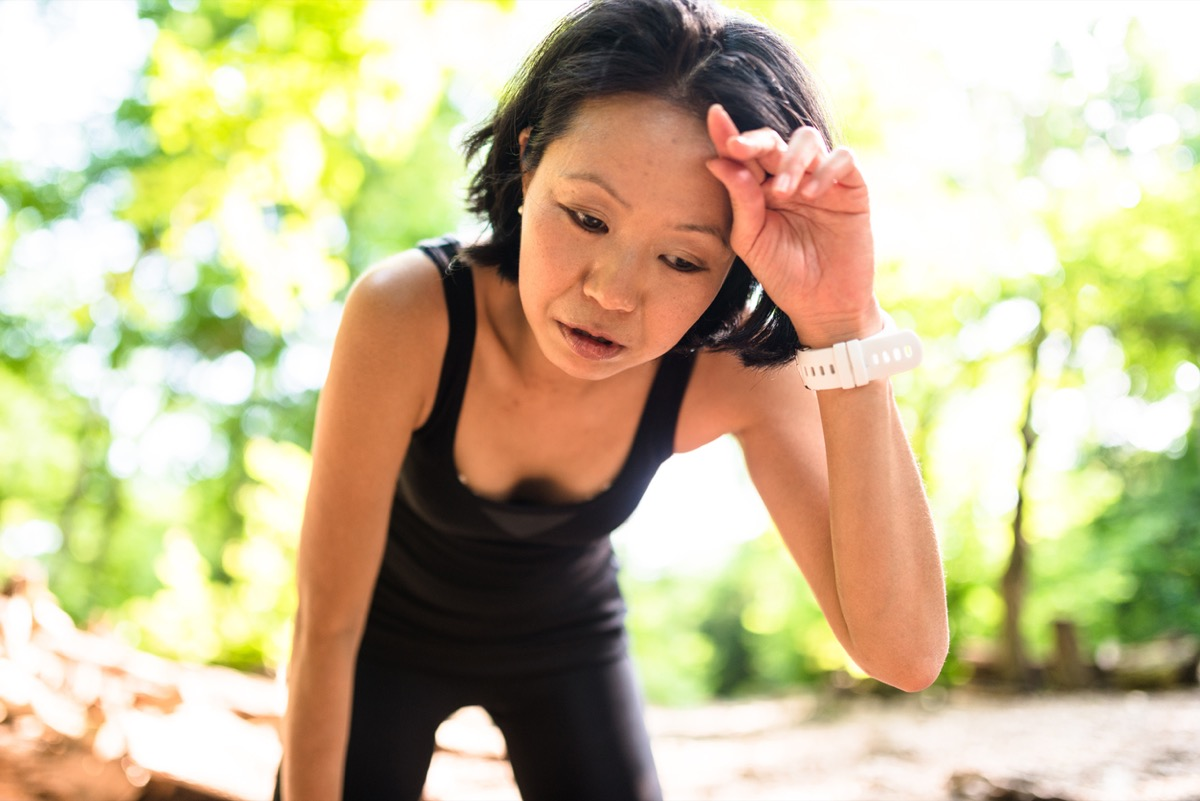 tired asian woman wiping her brow on an outdoor hike