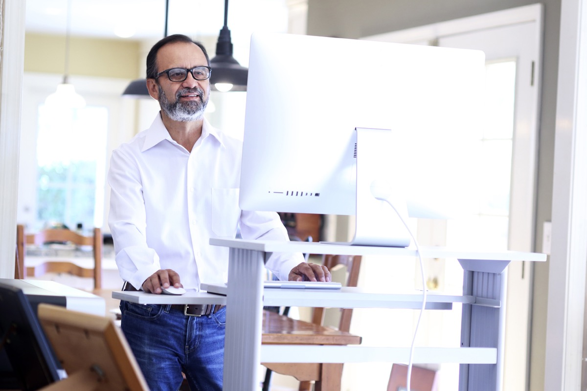 middle aged latino man working at a standing desk in his home