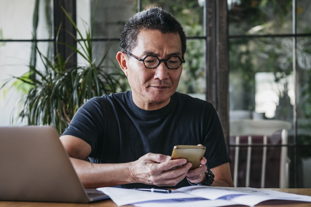 Chinese man in his 50s working remotely, using mobile phone, communication, connections, technology