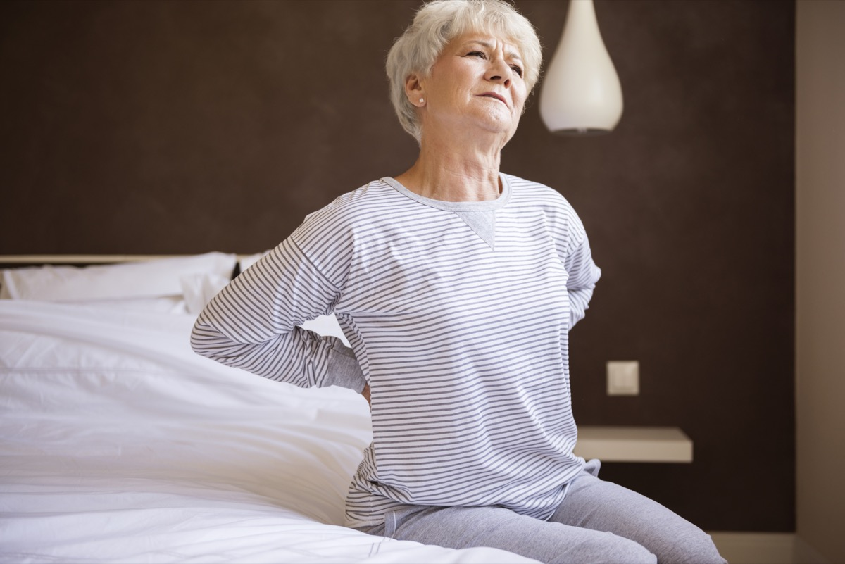 older white woman with back pain in bed