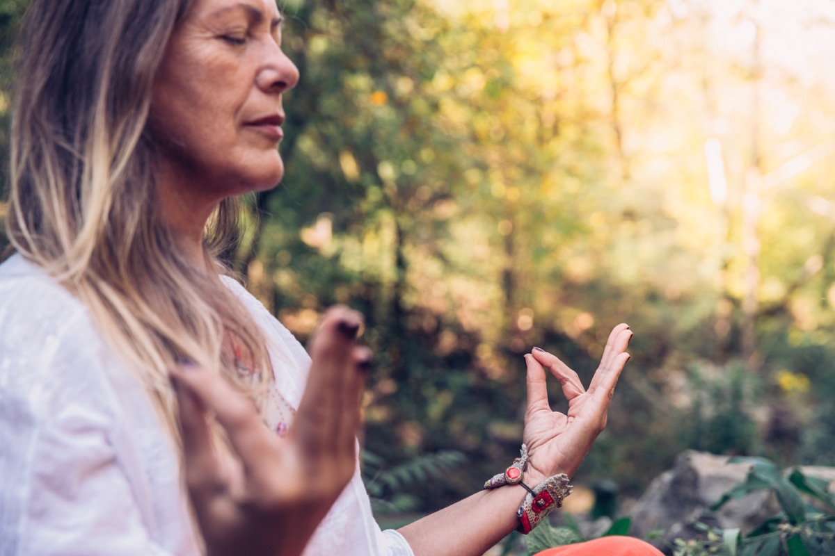 Mature Woman Meditating in Forest.