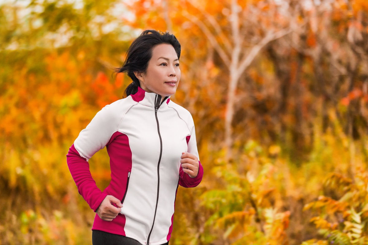 asian woman running in woods